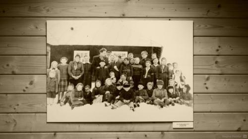 Dzieci z nauczycielem przed szkołą w Nowicy.